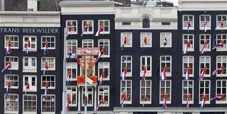 Dutch national flags hang from windows overlooking Central Station in Amsterdam April 28, 2013. REUTERS/Cris Toala Olivares