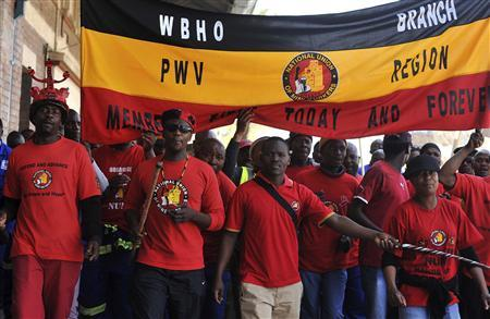 Members of the National Union of Mineworkers (NUM) take part in a strike in the central business district area of Johannesburg, August 27, 2013. REUTERS/Ihsaan Haffejee
