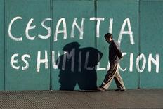 Una persona camina frente a un anuncio contrario al desempleo en el centro de Santiago, feb 11 2009. La tasa de desempleo en Chile bajó a un histórico nivel de 5,7 por ciento en el trimestre móvil mayo-julio, en lo que es el menor registro en al menos una década y una sorpresa para el mercado que esperaba una leve alza. REUTERS/Ivan Alvarado
