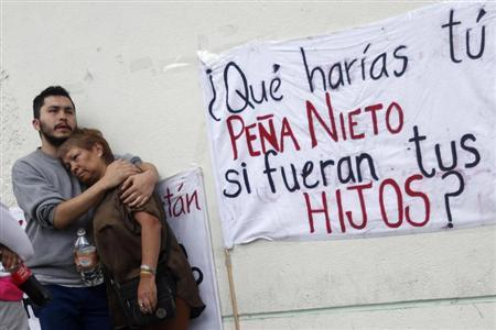Relatives of one of 12 people abducted in May, mourn outside the Attorney General building in Mexico City August 23, 2013. The banner reads, ''Pena Nieto, what would you do if they were your children?''. REUTERS/Edgard Garrido