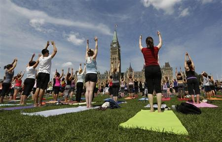 People take part in a free weekly yoga class on the front lawn of Parliament Hill in Ottawa July 31, 2013. REUTERS/Chris Wattie