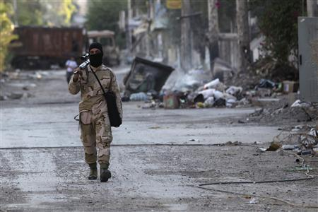 A Free Syrian Army fighter walks with his weapon on a street in Deir al-Zor August 30, 2013. REUTERS/Khalil Ashawi