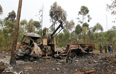 Congolese armed forces (FARDC) soldiers assess remains of a shelled truck used by M23 rebels after fighting them out of Kibati, outside Goma in the eastern Democratic Republic of Congo, August 30, 2013. REUTERS/Thomas Mukoya