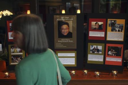 A woman walks past an informational booth detailing the life of Kenneth Bae during a vigil for Bae in Seattle, Washington August 10, 2013. REUTERS/Matt Mills McKnight