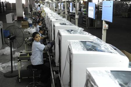Employees assemble washing machines on the production line inside a factory of Hefei Rongshida Sanyo Electric in Hefei, Anhui province August 13, 2013. REUTERS/Stringer