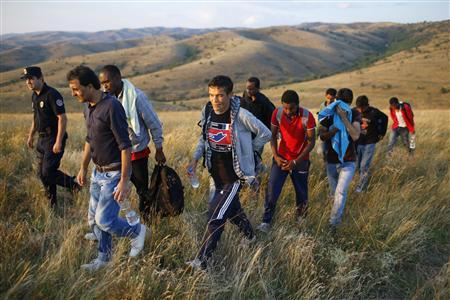 Migrants are escorted by a Serbian border policeman after being apprehended, having illegally entered the country from Macedonia, near the town of Presevo some 383 km (238 miles) from capital Belgrade, July 17, 2013. REUTERS-Marko Djurica