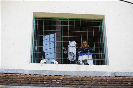 An asylum seeker looks out of a window at the asylum center in the village of Bogovadja, some 70 km (43 miles) from Serbia's capital Belgrade, July 23, 2013. REUTERS-Marko Djurica