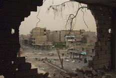 """Pessoas caminham por uma rua vista através de escombros de um prédio em Deir al-Zor, na Síria, em abril de 2013. A Síria saudou o """"recuo histórico norte-americano"""", neste domingo, depois que o presidente Barack Obama atrasou um ataque militar iminente, decidindo consultar o Congresso. 04/04/2013 REUTERS/ Khalil Ashawi"""