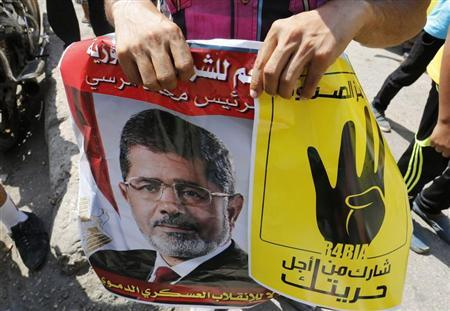 Supporters of ousted Egyptian president Mohamed Mursi hold his picture and a poster (R) showing the ''Rabaa'' or ''four'' gesture, in reference to the police clearing of the Rabaa al-Adawiya protest camp on August 14, during a protest against the military and the interior ministry at the Mohandiseen district in Cairo August 30, 2013. REUTERS/Louafi Larbi