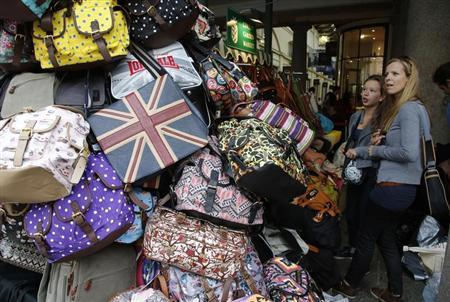 Shoppers browse handbags for sale at Covent Garden market in central London August 6, 2013. REUTERS/Chris Helgren