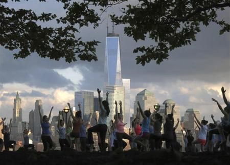 People stretch as they take part in a yoga class across the Hudson River from New York's Lower Manhattan and One World Trade Center in a park in Hoboken, New Jersey, June 11, 2013. REUTERS/Gary Hershorn/Files