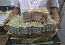 An employee poses with the bundles of Indian rupee notes inside a bank in Agartala, the capital of India's northeastern state of Tripura August 22, 2013. REUTERS/Jayanta Dey