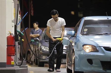 A motorist pumps petrol at a gas station in Kuala Lumpur July 15, 2010. REUTERS/Bazuki Muhammad/Files