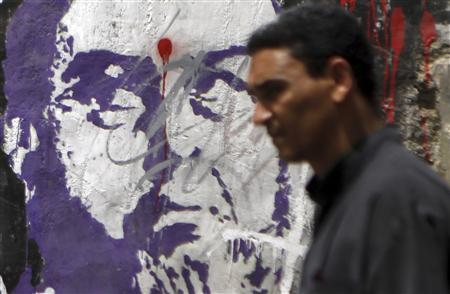 A man walks past graffiti depicting the Deputy Guide of the Muslim Brotherhood Khairat Al-Shater in downtown Cairo September 2, 2013. REUTERS/Amr Abdallah Dalsh