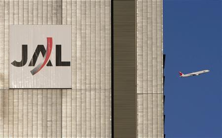 A Japan Airlines (JAL) aircraft flies near a JAL building at Tokyo's Haneda Airport in this October 27, 2009 file picture. REUTERS/Toru Hanai/Files