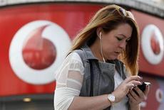 Mulher fala em celular enquanto passa por loja da Vodafone em Londres, 2 de setembro de 2013. A Verizon Communications está pronta para assumir o controle total da sua operadora de telefonia móvel nos Estados Unidos, em um acordo de 130 bilhões de dólares para comprar a fatia que a parceira europeia Vodafone tem na Verizon Wireless, acabando com um impasse empresarial que já durava uma década. REUTERS/Stefan Wermuth