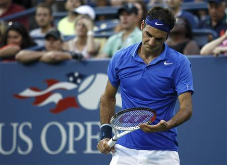 Roger Federer of Switzerland looks down at his racquet during the second set against Tommy Robredo of Spain at the U.S. Open tennis championships in New York September 2, 2013. REUTERS/Eduardo Munoz