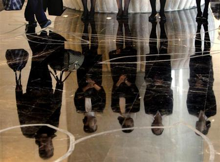 A porter carries luggage past a group of reception staff that are reflected in the floor as they stand in the foyer of the five-star rated Sofitel Hotel in Beijing November 19, 2007. REUTERS/David Gray/Files