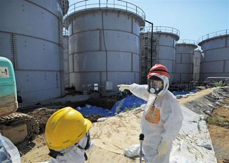 Japan's Economy, Trade and Industry Minister Toshimitsu Motegi (R), wearing a protective suit and a mask, inspects contaminated water tanks at the tsunami-crippled Fukushima Daiichi nuclear power plant in Fukushima prefecture August 26, 2013, in this photo released by Kyodo. REUTERS/Kyodo