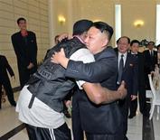 Лидер Северной Кореи Ким Чен Ын обнимает легенду баскетбола Денниса Родмана на встрече в Пхеньяне на фото, сделанном информационным агентством КНДР 1 марта 2013 года. Экстравагантный экс-баскетболист NBA снова держит путь в Северную Корею, второй раз за год, но открещивается от предоположений, что целью являются переговоры об освобождении заключенного американского миссионера. REUTERS/KCNA