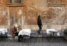 A woman eats a sandwich during lunch time downtown in Rome April 18, 2012. REUTERS/Tony Gentile