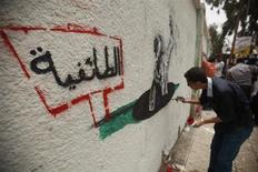 فنان يمني يرسم على جدار لوحة تندد بالطائفية في شارع بصنعاء يوم 24 أغسطس اب 2013. تصوير: خالد عبد الله - رويترز