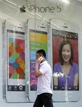Imagen de archivo de un hombre conversando por un teléfono mientras pasa frente a un anuncio de un iPhone en Pekín, jul 24 2013. Apple Inc envió el martes invitaciones oficiales para un evento el 10 de septiembre cuando se espera que lance su último iPhone, posiblemente en colores distintos a los característicos blanco y negro. REUTERS/Kim Kyung-Hoon