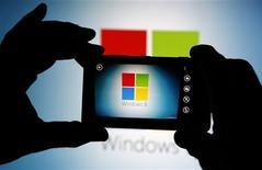 Un hombre utiliza la cámara de un teléfono Lumia 820 de Nokia para fotografiar el símbolo de Windows 8 en Zenica, Bosnia y Herzegovina, sep 3 2013. Microsoft Corp llegó a un acuerdo para comprar el negocio de teléfonos de Nokia por 7.200 millones de dólares, pero no hay garantía de que adquiriendo al pionero de los teléfonos celulares acelere su lento paso desde una compañía de software de computadoras personales hacia la computación móvil. REUTERS/Dado Ruvic