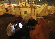Imagen de archivo de unos manifestantes utilizando un ordenador portátil durante una protesta en la plaza Tahrir de El Cairo, nov 28 2012. La guerra civil en Siria y las pugnas políticas en Egipto han abierto nuevos campos de batalla en internet y han provocado un alza de los ciberataques en Oriente Medio, informó McAfee. REUTERS/Amr Abdallah Dalsh
