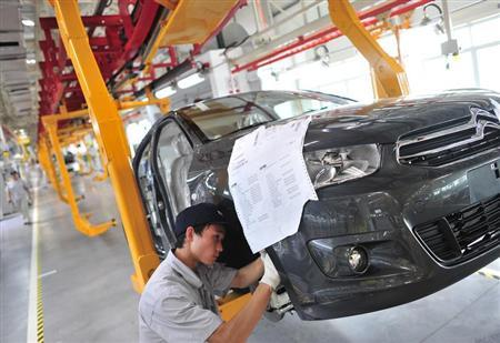 An employee works at the third factory of Dongfeng Peugeot Citroen Automobile company, after its inauguration ceremony, in Wuhan, July 2, 2013. REUTERS/China Daily