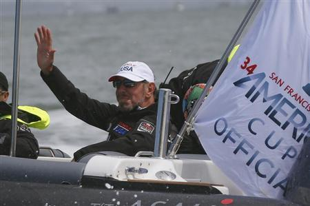 Oracle Corporation co-founder and CEO Larry Ellison waves to a passing boat prior to the first race of the Louis Vuitton Cup challenger series yacht race in San Francisco, California August 17, 2013. REUTERS/Peter Andrews