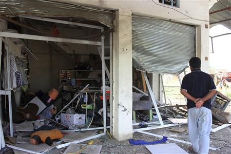 A man looks at a shop, site of a car bomb attack in Hilla, around 100 km (62 miles) south of Baghdad September 3, 2013. REUTERS/Habib