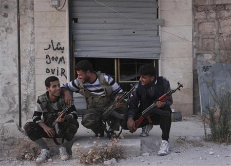 Free Syrian Army fighters react as they sit together along a street in Kansafra in Idlib province September 3, 2013. REUTERS/Loubna Mrie