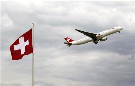 An Airbus A 330-343E of Swiss airlines takes-off past a Swiss national flag from the airport in Zurich October 4, 2012. REUTERS/Arnd Wiegmann