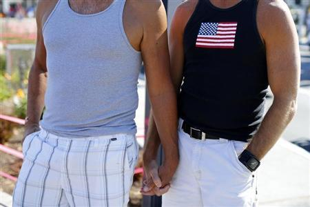 A gay couple holds hands during a rally in support of the United States Supreme Court decision on marriage rights in San Diego, California June 26, 2013. REUTERS/Mike Blake