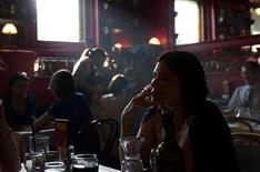 Женщина курит в московском кафе 31 мая 2013 года. Деловая активность в секторе услуг РФ продемонстрировала скромный рост на фоне устойчивого роста новых заказов, возобновления роста занятости и ускорения темпов инфляции закупочных цен до восьмимесячного максимума, свидетельствуют данные исследования Markit, проведенного по заказу HSBC. REUTERS/Maxim Shemetov