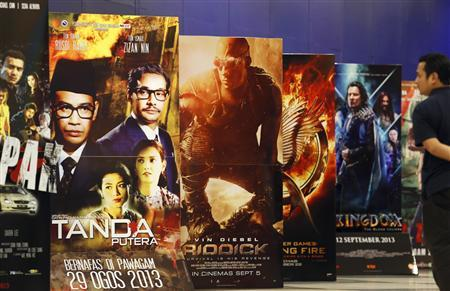 A movie-goer looks at the ''Tanda Putera'' poster (2nd L) among other movie posters at a cinema in Putrajaya outside Kuala Lumpur August 29, 2013. REUTERS/Bazuki Muhammad