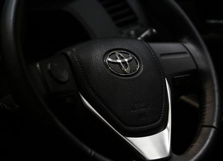 The logo of Toyota Motor Corp. is seen on a steering wheel of the company's car at the Toyota Motor's showroom in Tokyo August 1, 2013. REUTERS/Issei Kato