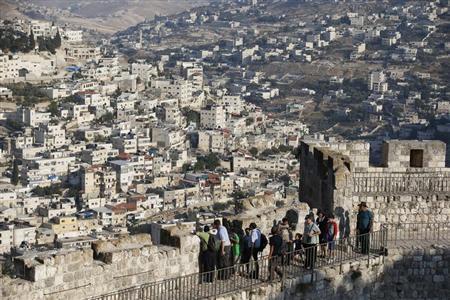Arab neighbourhoods in East Jerusalem are seen in the background as tourists walk atop a wall surrounding Jerusalem's Old City August 13, 2013. REUTERS/Ronen Zvulun