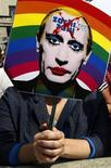 """Участник акции протеста против закона о запрете гей-пропаганды с плакатом, на котором изображен президент России Владимир Путин, в центре Лондона 10 августа 2013 года. Президент России Владимир Путин сказал, что у него """"абсолютно нормальные"""" отношения с подчиненными-гомосексуалистами, признал их заслуги перед страной и назвал проблему преследования гей-активистов в России раздутой, пообещав не карать за радужный флаг ЛГБТ-сообщества законом о запрете гей-пропаганды. REUTERS/Luke MacGregor"""