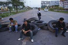 Крестьяне забаррикадировали дорогу во время акции протеста в тайском городе Сураттани 4 сентября 2013 года. Десятки тысяч таиландских крестьян, протестующих из-за резкого падения цен на натуральный каучук, начали в среду перекрывать дороги, угрожая передвижению между основными транспортными и туристическими центрами страны. REUTERS/Athit Perawongmetha