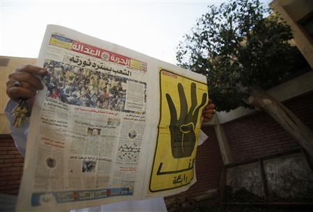 A man reads the Muslim Brotherhood's newspaper Al-Hurriya wa-l-adala (Freedom of Justice), named after their political party, in Cairo, September 3, 2013. Whenever Muslim Brotherhood journalist Islam Tawfiq files a story about the group's struggle for survival for its newspaper Freedom and Justice, he fears his Internet address will tip off state security agents to his whereabouts. Thousands of Brotherhood members have been arrested in a widening crackdown on the group since the army deposed Islamist President Mohamed Mursi on July 3. Reporters for the newspaper, which still appears in a tiny fraction of its previous circulation, see themselves as the last people left to tell the Brotherhood's side of the story in a country dominated by media that back the military crackdown. The price, the journalists say, is an underground existence, moving from place to place, communicating from Internet cafes, rarely seeing family or friends. The newspaper's headline (L) reads: ''People recover their revolution,'' and the words on the yellow page read: ''All of us are Rabaa''. Picture taken September 3, 2013. REUTERS/Amr Abdallah Dalsh