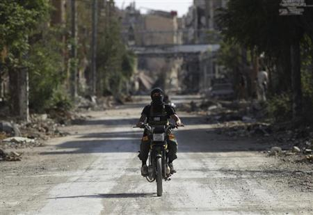 A fighter from the Islamist Syrian rebel group Jabhat al-Nusra rides a motorcycle along a deserted street in Deir al-Zor August 17, 2013. REUTERS/Khalil Ashawi