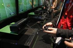 """Посетители выставки Gamescom 2013 играют в """"FIFA 14"""" на консолях Xbox One в Кёльне 21 августа 2013 года. Многие магазины уже получили предзаказы на все имеющиеся в наличии новые игровые консоли Xbox One от Microsoft Corp, сообщил в интервью Рейтер Юсуф Мехди, вице-президент подразделения американской компании, занимающегося Xbox. REUTERS/Ina Fassbender"""