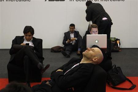 A visitor rests while others work during the Mobile World Congress in Barcelona, February 26, 2013. REUTERS/Gustau Nacarino/Files