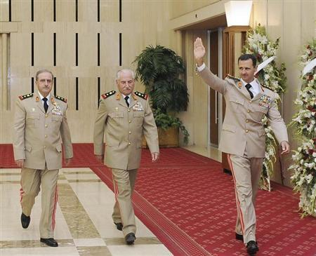 Syria's President Bashar al-Assad (R) waves as he arrives with Syrian Defense Minister General Ali Habib (C) and Chief of Staff General Dawoud Rajha to attend a dinner to honour army officers on the 65th Army Foundation anniversary in Damascus August 1, 2010. REUTERS/Sana/Files