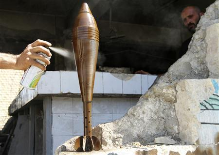 A Free Syrian Army fighter spray paints an improvised mortar shell, as his fellow fighter watches him, in Aleppo September 4, 2013. REUTERS/Hamid Khatib