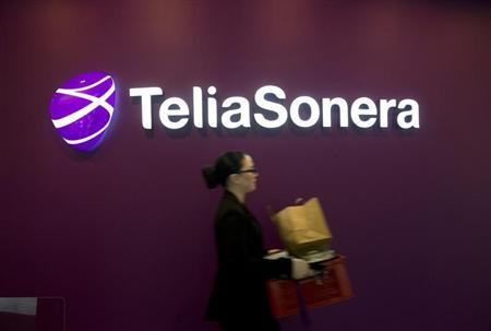 A woman walks past TeliaSonera's logo during the company's fourth quarter result presentation January 31, 2013 in this picture provided by Scanpix. REUTERS/Fredrik Sandberg/Scanpix