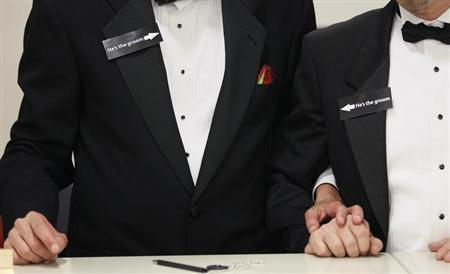 Two men, both wearing signs that read ''he's the groom'', hold hands shortly after midnight after getting a civil union when Colorado's civil union law went into effect in Denver May 1, 2013. REUTERS/Rick Wilking