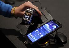 """Un periodisa observa el reloj Galaxy Gear de Samsung junto a un teléfono Galaxy Note 3 de la misma firma, durante su lanzamiento en Berlín, sep 4 2013. Samsung Electronics Co Ltd presentó el miércoles un """"reloj inteligente"""" que funciona como accesorio de su popular smartphone Galaxy, y que cuenta con una pequeña pantalla que brinda funciones básicas como foto, llamadas """"manos libres"""" y mensajería instantánea. REUTERS/Tobias Schwarz"""